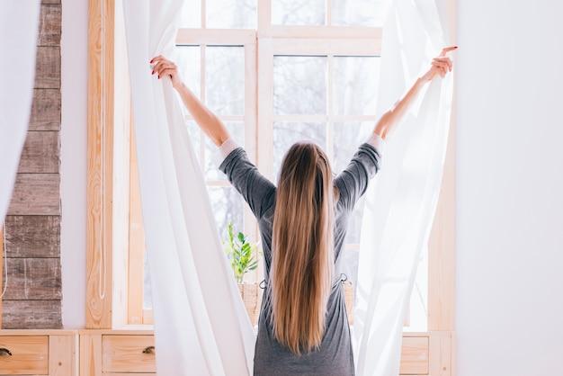 Chica abriendo cortinas