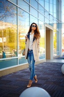 Chica en un abrigo beige y jeans azules