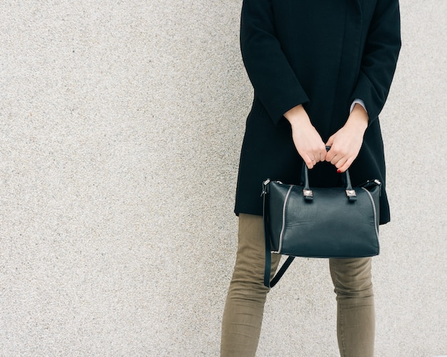 Chica con abrigo negro, jeans verdes y una bolsa en la mano se encuentra en una superficie de pared beige