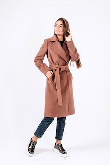 Chica en abrigo de otoño sobre un fondo blanco.