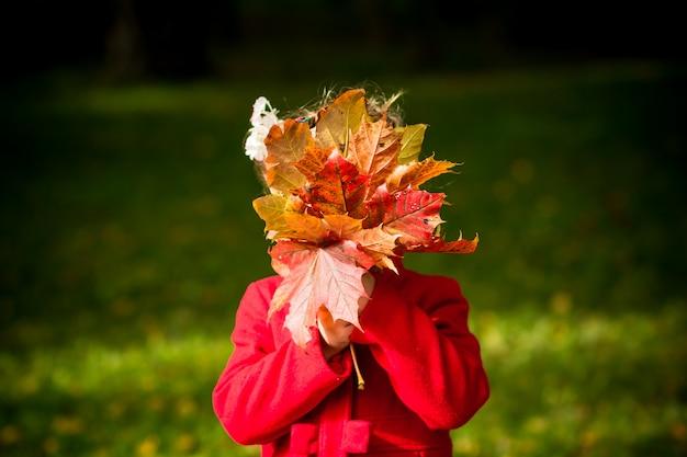Chica con abrigo rojo con hojas de otoño en el parque de belleza