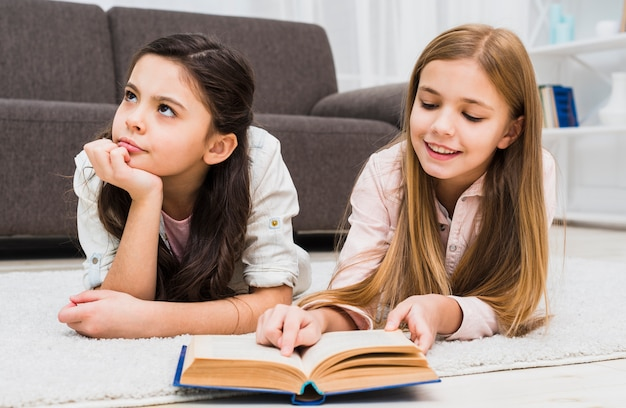 Chica aburrida acostada con su amiga leyendo el libro en la sala de estar