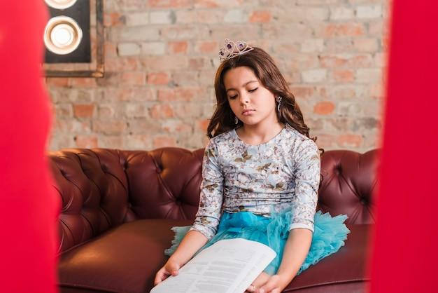 Chica aburrida sentada en el sofá en el backstage con guiones