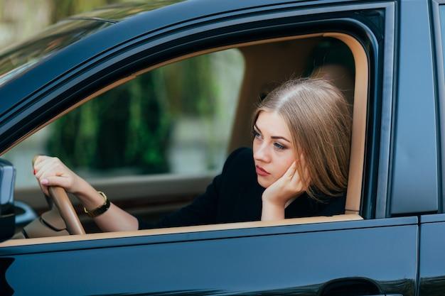 Chica aburrida en su coche en el atasco de tráfico