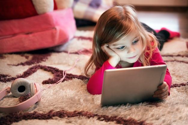 Chica aburrida usando tableta en la alfombra