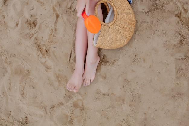 Chica aceite en aerosol bronceando sus piernas protección contra los rayos ultravioleta del sol poniéndose protector solar bloqueador solar.