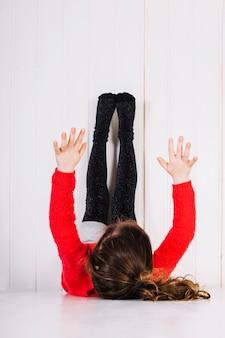 Chica acostada en el piso con las piernas hacia arriba