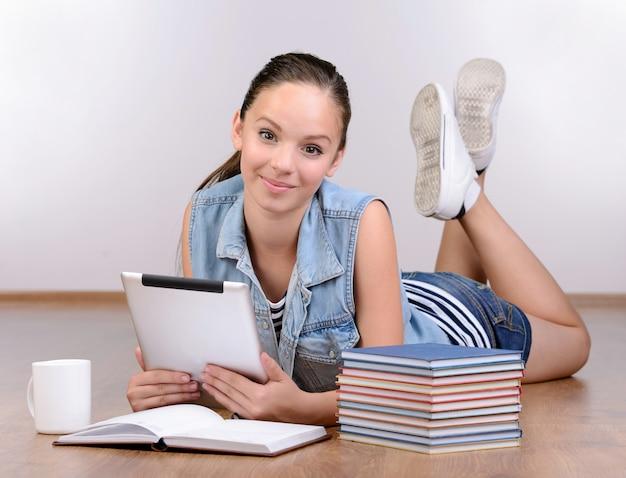 Chica acostada en el piso y usando una tableta digital.