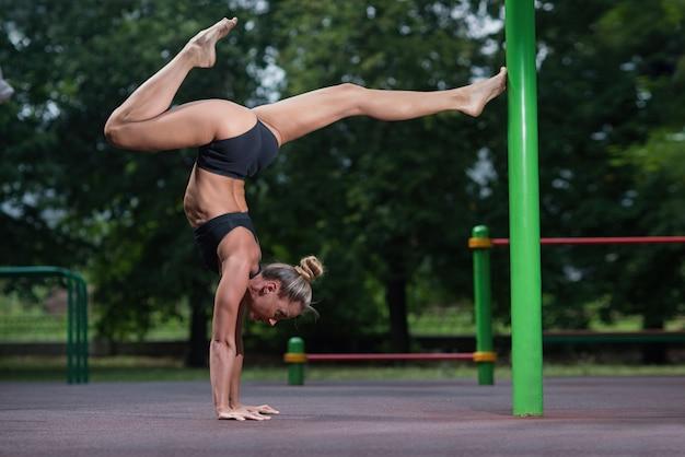 Chica de acrobacia deportiva se para en sus manos y hace un elemento acrobático