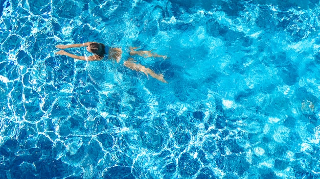 Chica activa en la piscina vista aérea drone desde arriba, joven nada en agua azul, vacaciones tropicales, vacaciones en concepto de resort