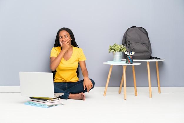 Chica adolescente afroamericana estudiante con largo cabello trenzado sentado en el suelo pensando una idea