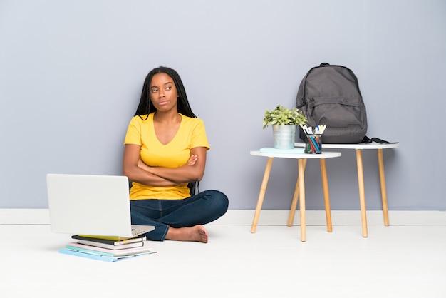 Chica adolescente afroamericana estudiante con largo cabello trenzado sentado en el suelo pensando en una idea