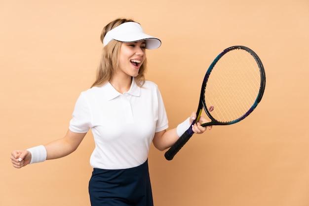 Chica adolescente aislada en beige jugando tenis y celebrando una victoria