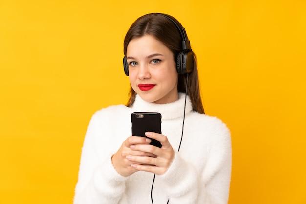 Chica adolescente aislada en la pared amarilla escuchando música con un móvil y mirando al frente