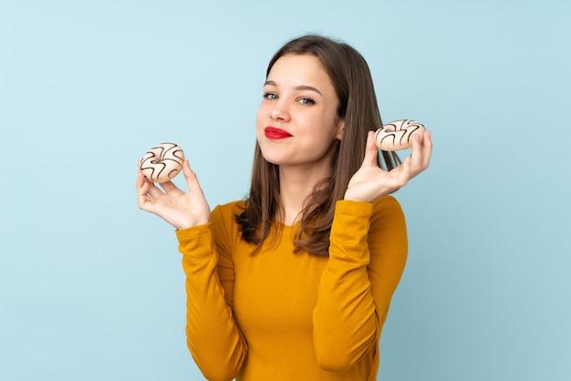 Chica adolescente aislada en la pared azul con donas con expresión feliz