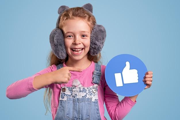 Chica adolescente alegre en ropa casual y orejeras mullidas apuntando al pulgar hacia arriba