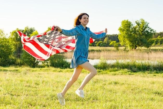 Chica adolescente con bandera americana corriendo