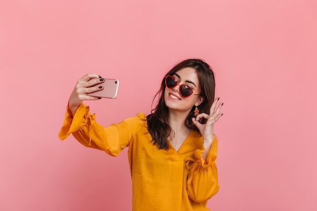 Chica adolescente en blusa brillante y gafas de sol inusuales muestra el signo