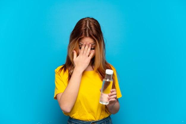 Chica adolescente con una botella de agua sobre fondo azul aislado con expresión cansada y enferma