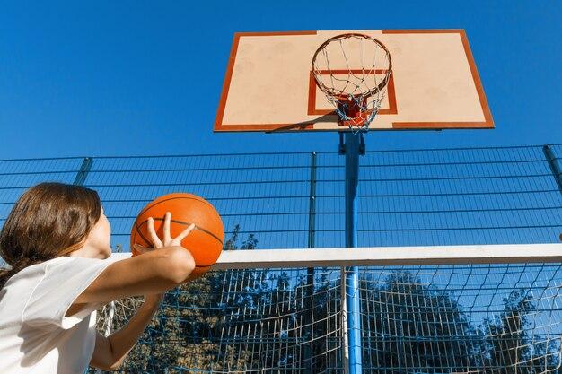 Chica adolescente calle jugador de baloncesto con pelota