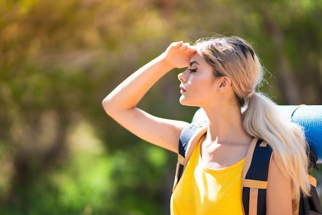 Chica adolescente caminando al aire libre mirando lejos con la mano para mirar algo