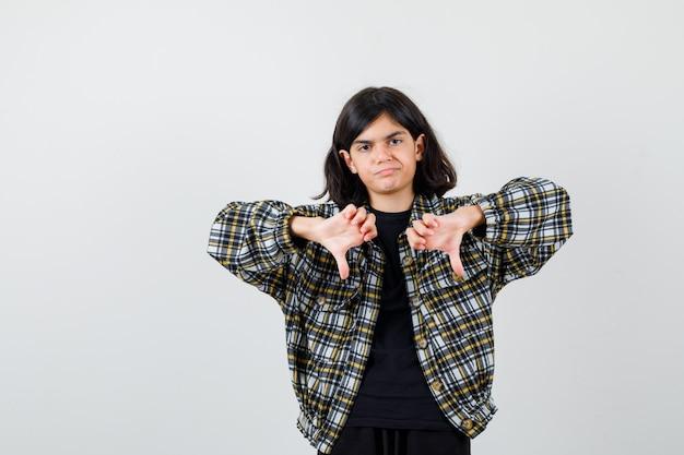 Chica adolescente en camisa casual apuntando hacia abajo con los pulgares y mirando triste, vista frontal.