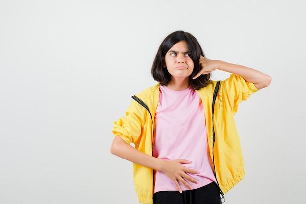 Chica adolescente en camiseta, chaqueta manteniendo la mano sobre el estómago, mostrando el gesto del teléfono y mirando vacilante, vista frontal.