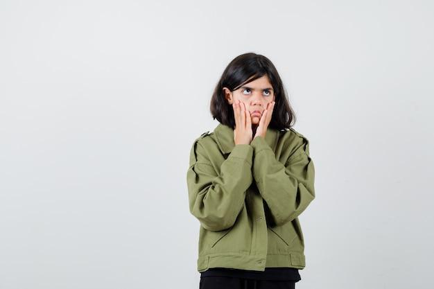 Chica adolescente en camiseta, chaqueta tirando hacia abajo de su piel y mirando aburrida, vista frontal.