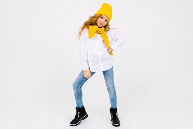 Chica adolescente caucásica soñando elegante y atractiva con una camisa blanca y pantalones vaqueros azules y un sombrero amarillo con botas sobre un fondo blanco de estudio con espacio de copia.