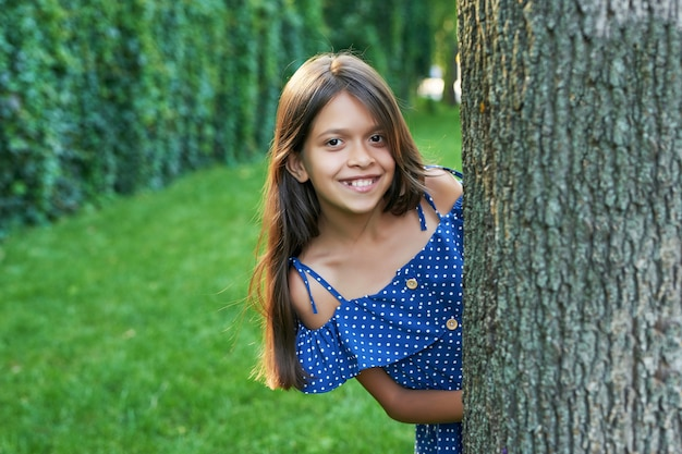 Chica adolescente cerca de un árbol en un parque de verano al atardecer