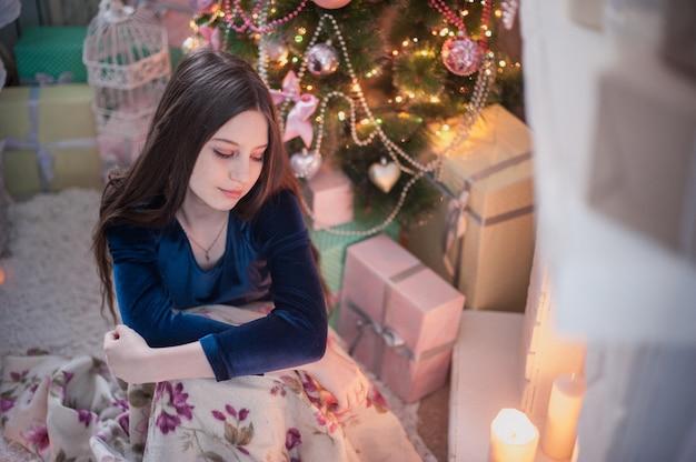 Chica adolescente cerca de la chimenea mira vela encendida