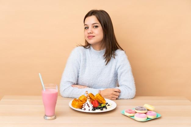 Chica adolescente comiendo gofres aislados en la pared de color beige con los brazos cruzados y mirando hacia adelante