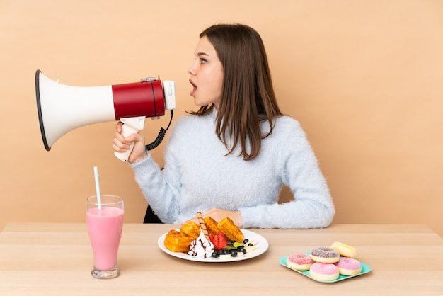 Chica adolescente comiendo gofres en la pared beige gritando a través de un megáfono