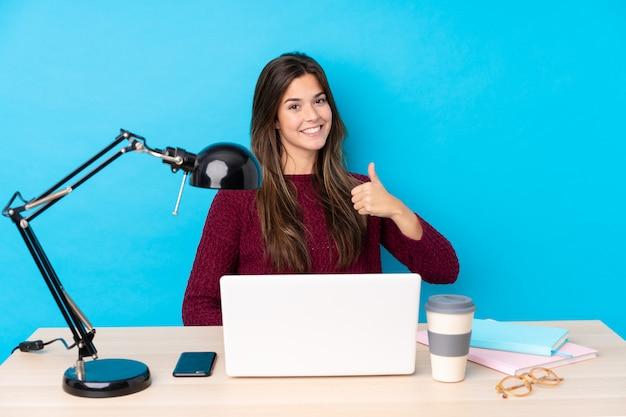 Chica adolescente con una computadora portátil en una mesa dando un gesto de pulgares arriba