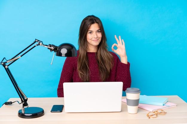Chica adolescente con una computadora portátil en una mesa mostrando un signo bien con los dedos