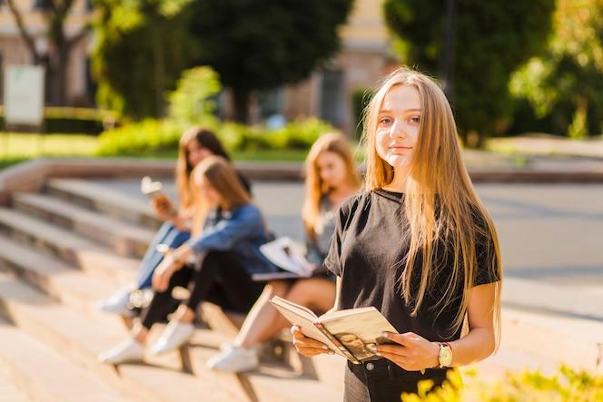 Chica adolescente con libro cerca de amigos