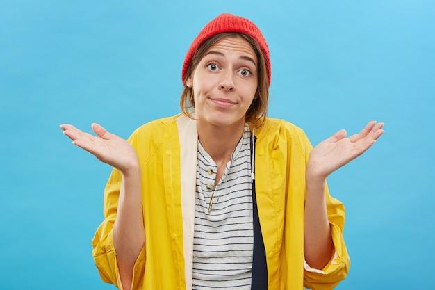 Chica adolescente despistada con elegante sombrero rojo e impermeable amarillo mirando con expresión de ojos abiertos en su rostro, encogiéndose de hombros en ignorancia o indiferencia, diciendo: cosas suceden