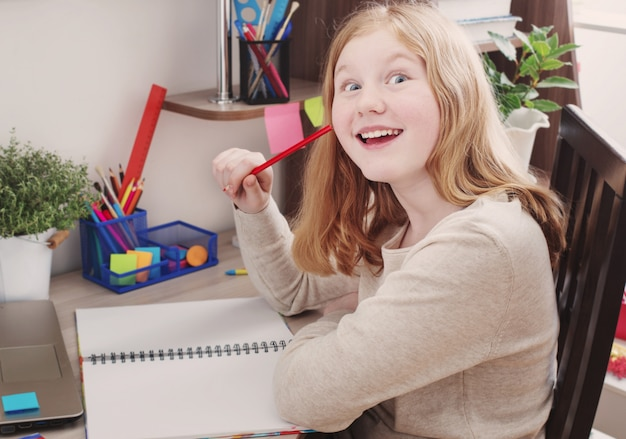 Chica adolescente dibuja en casa
