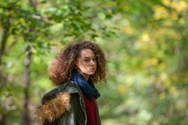 Chica adolescente en el parque de otoño