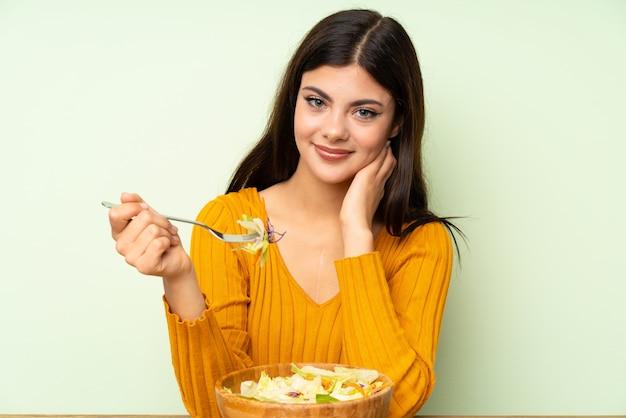 Chica adolescente con ensalada sobre pared verde