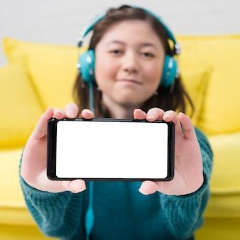 Chica adolescente enseñando smartphone