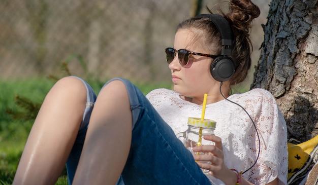 Chica adolescente escuchando música y bebiendo agua en el parque