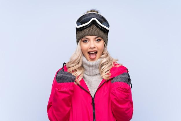 Chica adolescente esquiador con gafas de snowboard celebrando una victoria