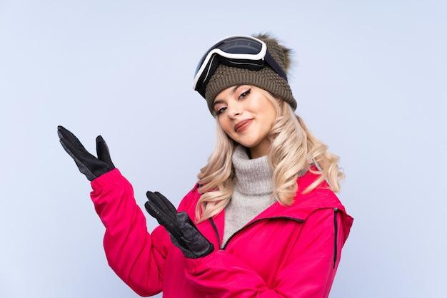 Chica adolescente esquiador con gafas de snowboard extendiendo las manos a un lado para invitar a venir