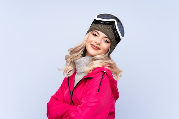 Chica adolescente esquiador con gafas de snowboard sobre risa azul aislado