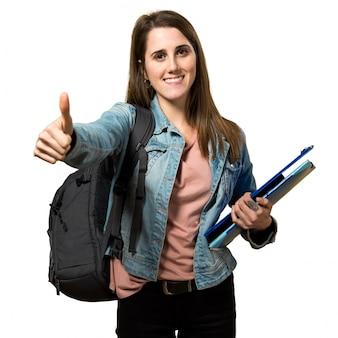 Chica adolescente estudiante sosteniendo libros y con el pulgar arriba