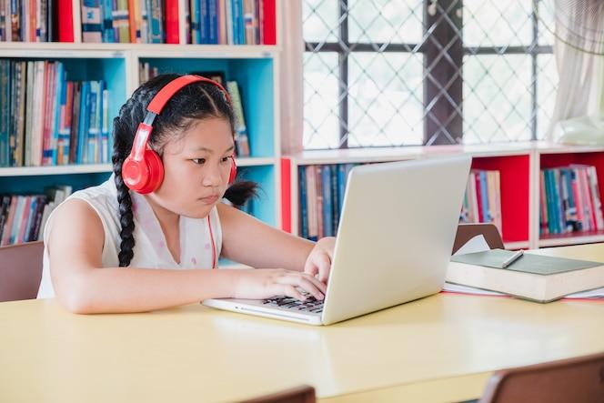 Chica adolescente estudiante usando la computadora portátil para la educación en la escuela.