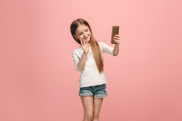 La chica adolescente feliz haciendo foto selfie por teléfono móvil