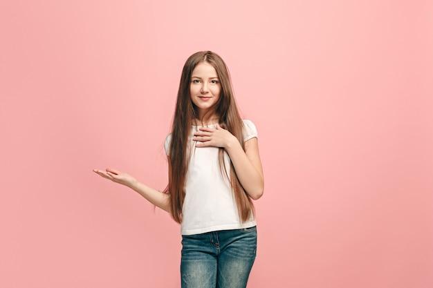 Chica adolescente feliz de pie y presentando algo, sonriendo aislado en la pared rosa de moda. hermoso retrato femenino de medio cuerpo. las emociones humanas, el concepto de expresión facial.