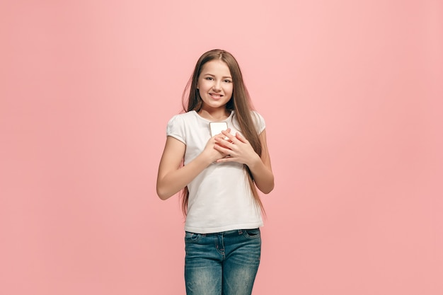 La chica adolescente feliz con teléfono de pie y sonriendo contra la pared rosa
